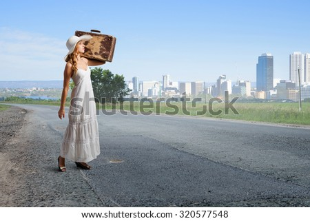 Woman with suitcase in white long dress and hat on asphalt  road