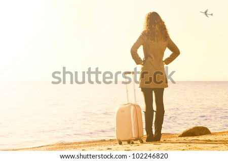 woman with suitcase is traveling at sea coast in winter - stock photo
