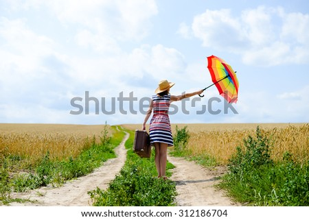 Woman with suitcase standing on road between field of wheat. Backview of girl in hat holding colorfull umbrella.