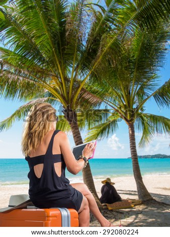Woman with suitcases and tablet on the tropical beach - stock photo