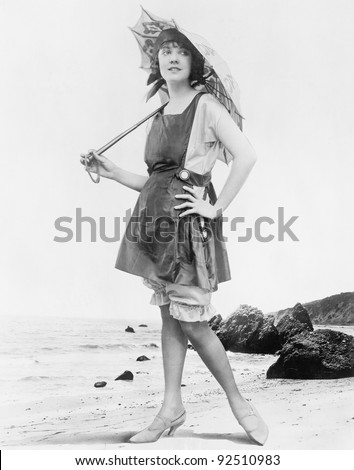 Woman with sun umbrella and bathing suit at the beach