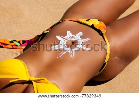 Woman with suncream on the belly at the beach in summer - stock photo