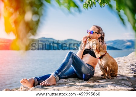Woman with sunglasses wearing black bikini and jeans drinking coffee and eating cookies on the beach with her small yellow dog - stock photo