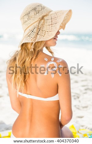 Woman with sunscreen on her skin on a sunny day - stock photo