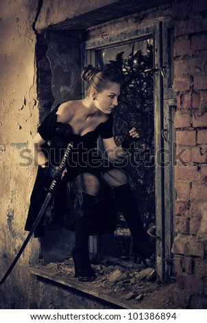 woman with sword at old building window - stock photo
