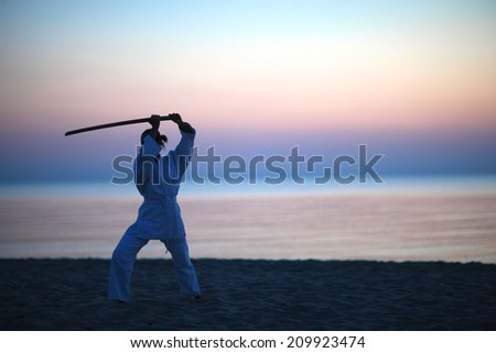 Woman with sword practicing self-defence technique on the beach  - stock photo