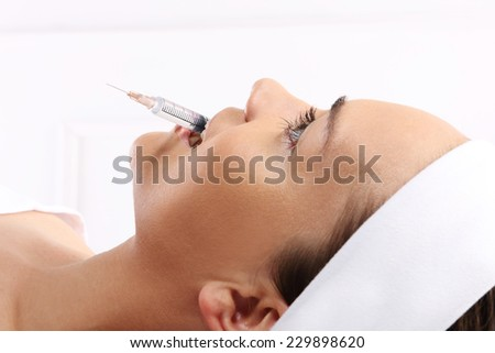 Woman with syringe. Portrait of a white woman during surgery filling facial wrinkles, Cosmetic is injected into facial skin cosmetics - stock photo
