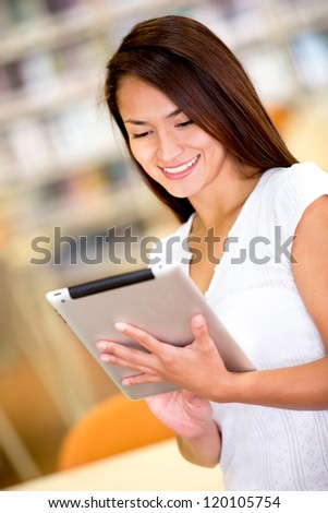 Woman with tablet computer reading a book - stock photo