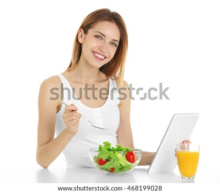 Woman with tablet eating healthy food on white background
