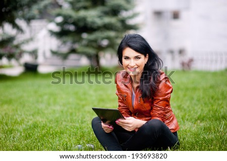 woman with tablet on the grass in the park