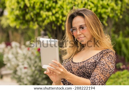 Woman with tablet outdoors wearing sunglasses and reading - stock photo