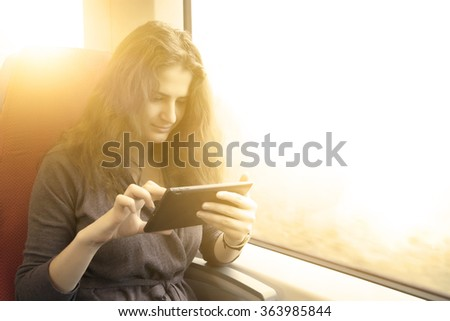 woman with tablet pc on a train ride - stock photo