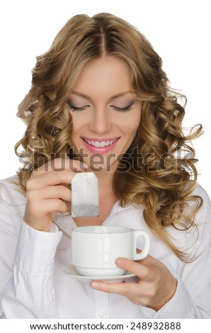 woman with tea bag looks into cup isolated on white