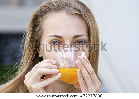 Woman with tea cup. Tea with sea buckthorn and honey on cafe background. Outdoors portrait.