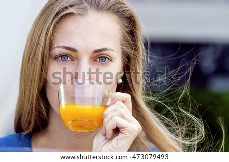 Woman with tea cup. Tea with sea buckthorn and honey on cafe background. Outdoors portrait. Filtered image, vintage style.