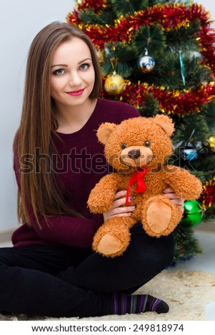Woman with teddy bear near the Christmas tree at room  - stock photo