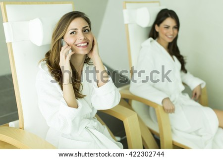 Woman with telephone and other woman in bathrobes relaxing in the spa
