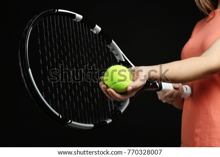 Woman with tennis racket and ball on black background