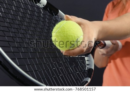 Woman with tennis racket and ball on dark grey background