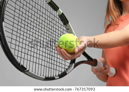Woman with tennis racket and ball on grey background
