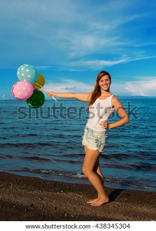 Woman with the balloons on the beach  - stock photo