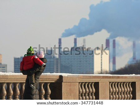 Woman with the child against pipes with a smoke - stock photo