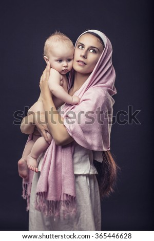 Woman with the covered head mother with a baby in her arms in Studio on a black background in the image of the virgin Mary - stock photo
