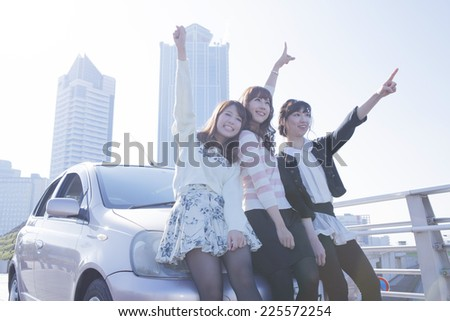 Woman with the friend in front of the car - stock photo