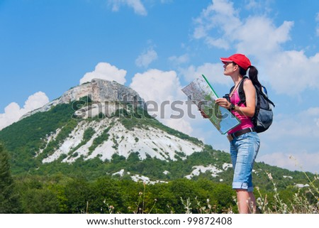 woman with the map and binoculars in the mountains - stock photo