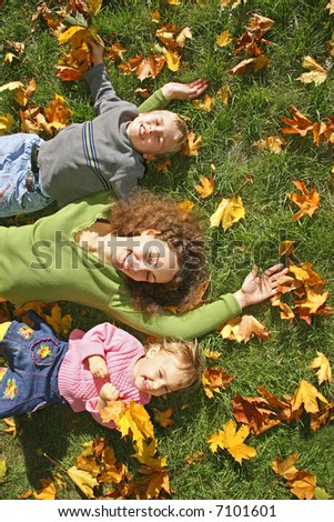 woman with the son and the daughter they lie on the grass - stock photo