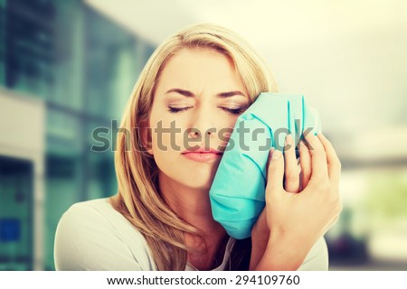 Woman with tooth ache holding an ice bag near her face - stock photo