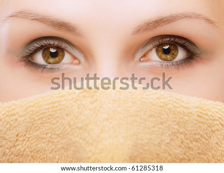 Woman, with towel wound round head and closing mouth, on white background. - stock photo