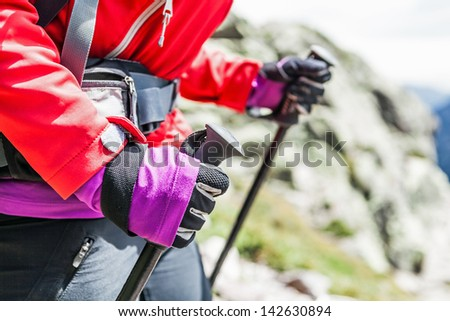 Woman with trekking sticks hiking with backpack in mountains, Corsica in France. Climber or mountaineer walking in high rocky mountains with equipment - stock photo