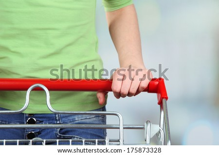 Woman with trolley in supermarket close-up