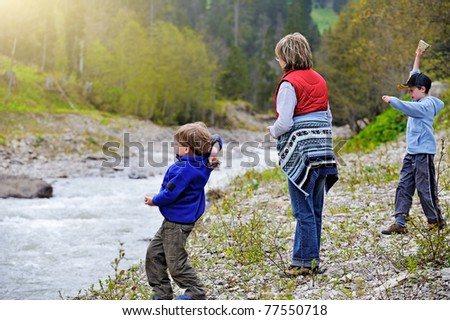 woman with two children gathering and throwing rocks at the river