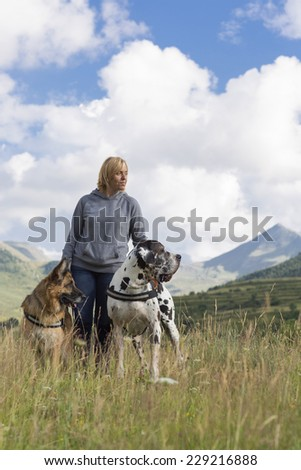 woman with two dogs, german sheperd and great dane in mountain. outdoor photo. - stock photo