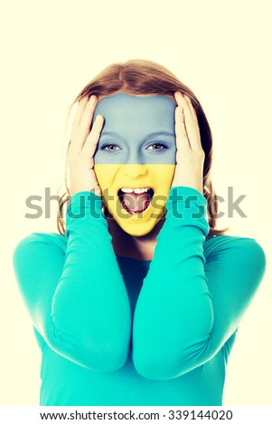 Woman with Ukraine flag painted on face. - stock photo