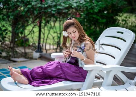 woman with Ukulele in garden - stock photo