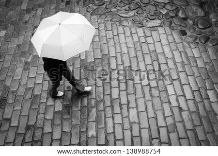Woman with umbrella in rain, old town - stock photo