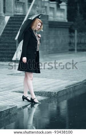 Woman with umbrella in the rain - stock photo