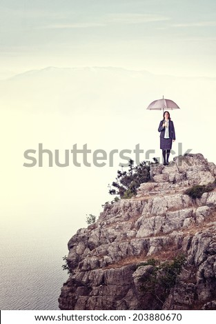 woman with umbrella on rock cliff