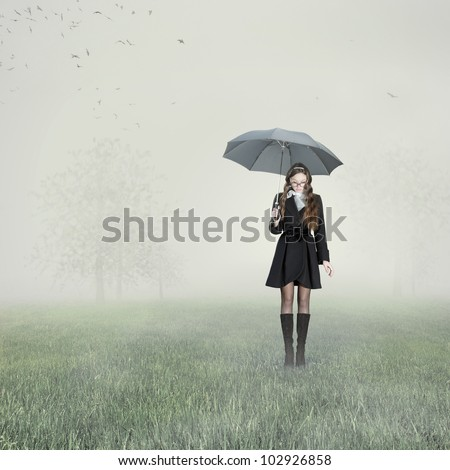 Woman with umbrella on the field - stock photo