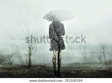 Woman with umbrella standing on the field with trees. The image with the effect of double exposure - stock photo