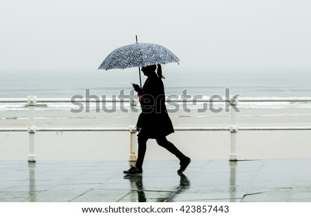 Woman with umbrella walking around the city