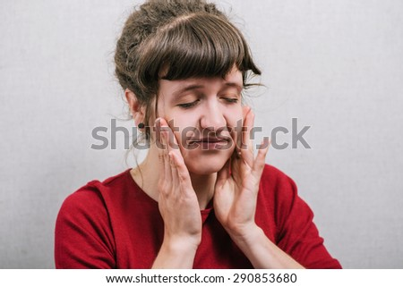 Woman with unhappy face. On a gray background. - stock photo