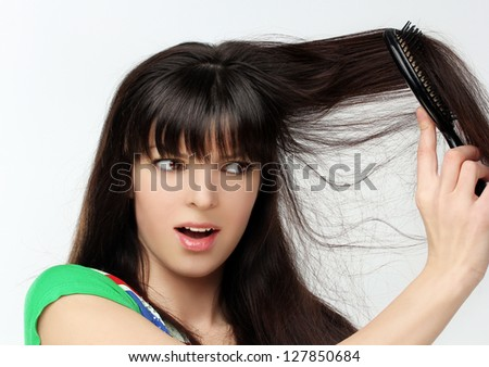 Woman with upset expression trying to get a brush out of her hair - stock photo