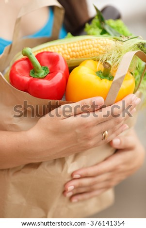 Woman with vegetables in shopping bag at street market, girl with organic food near supermarket, woman with bag of food at street market, selective focus, soft grain filter, series - stock photo