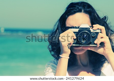 Woman with vintage retro camera having fun on the beach on blue sea background - stock photo