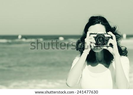 Woman with vintage retro camera having fun on the beach on blue sea background - stock photo
