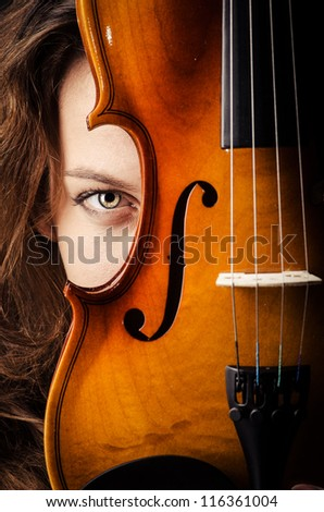 Woman with violin in dark room - stock photo